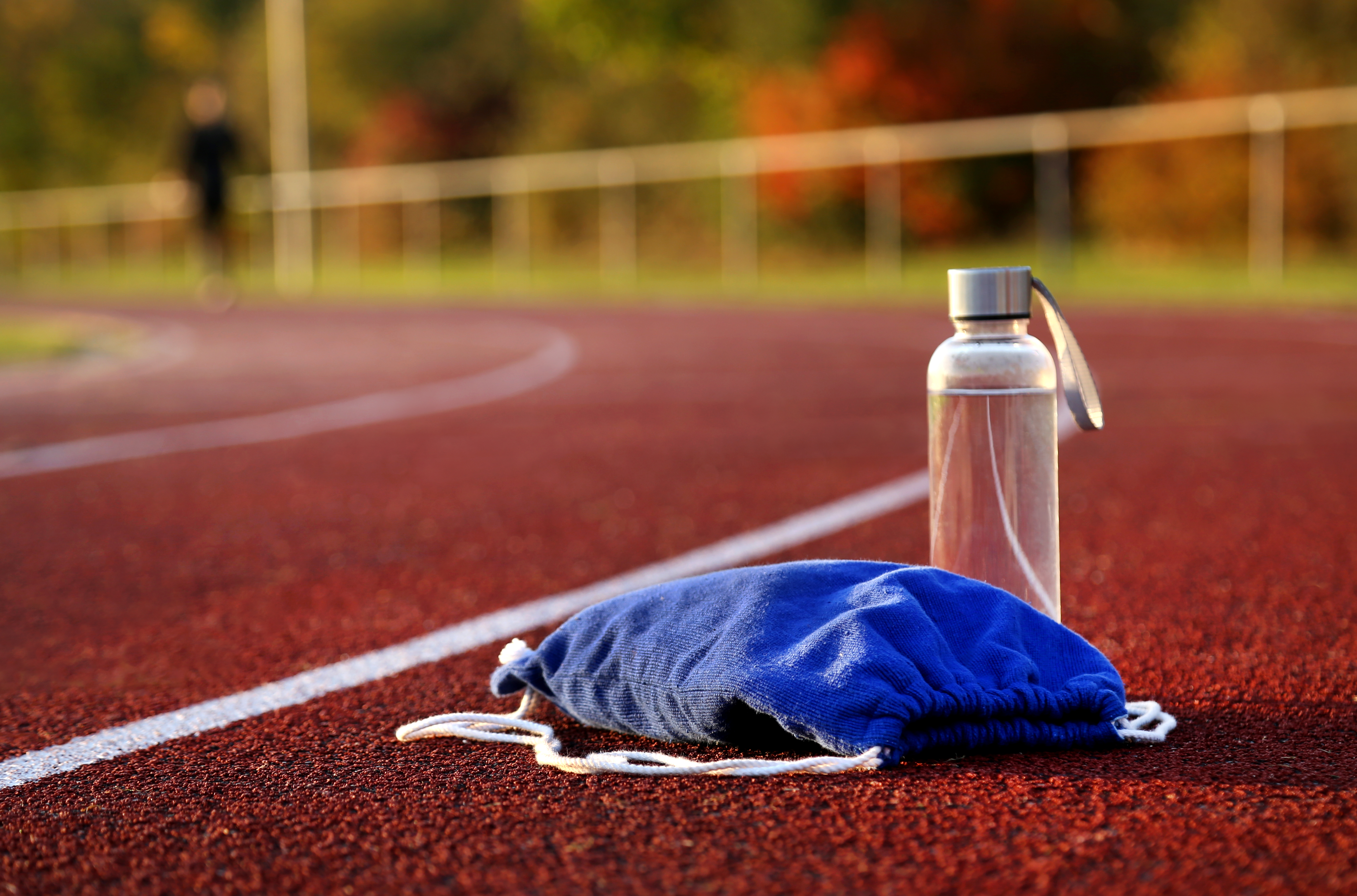 Rucksack and water bottle on athletic track at afternoon